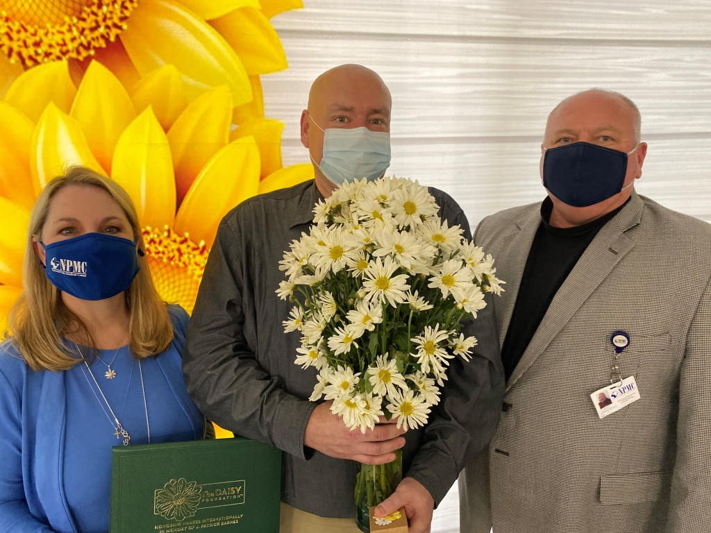 Inaugural NPMC Daisy Award Winner, Matt McFarland, RN, (center) with NPMC's CNO, Lisa Wallace (left) and CEO, Scott Smith (Right)